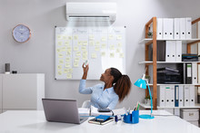 Businesswoman Operating Air Conditioner In Office