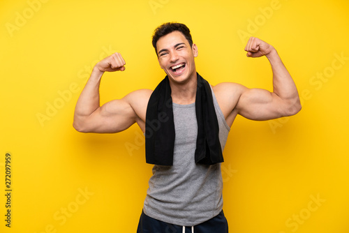 Fototapeta Handsome sport man over isolated background making strong gesture obraz