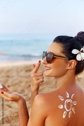 Beautiful Woman smile applying sun cream on face. Skincare. Body Sun protection. sunscreen. Female in hat smear moisturizing lotion on skin
