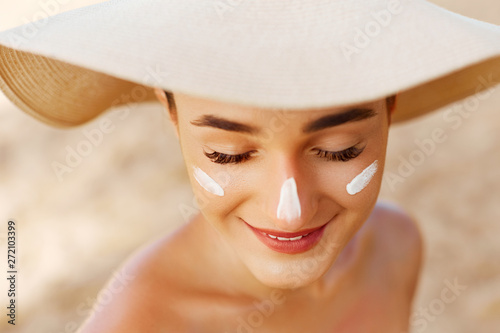 Beauty Woman smile applying sun cream on face. Skin care. Body Sun protection. sunscreen. Female in hat smear moisturizing lotion on skin