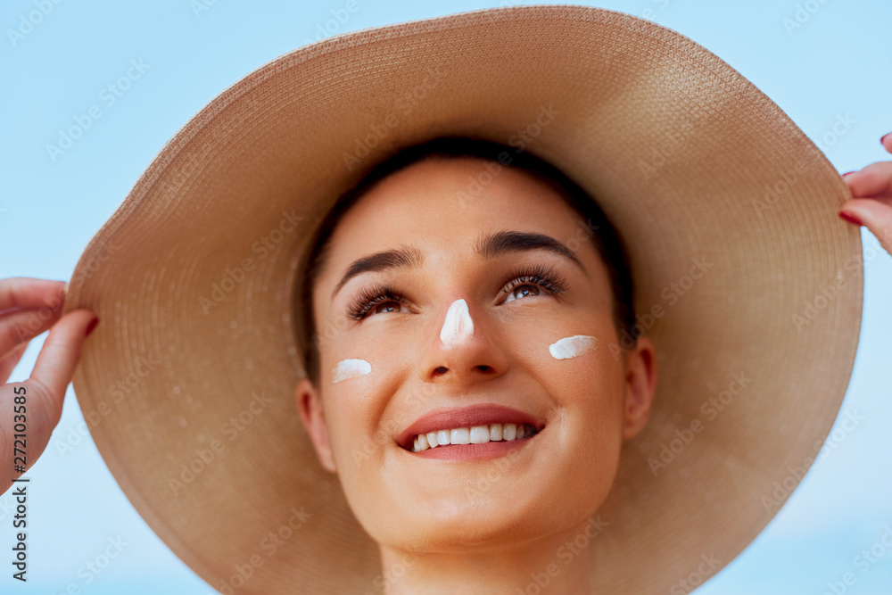 Fototapety, obrazy: Beauty Woman smile applying sun cream on face. Skin care. Body Sun protection. sunscreen. Female in hat smear moisturizing lotion on skin