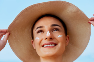 Beauty Woman smile applying sun cream on face. Skin care. Body Sun protection. sunscreen. Female in hat smear moisturizing lotion on skin