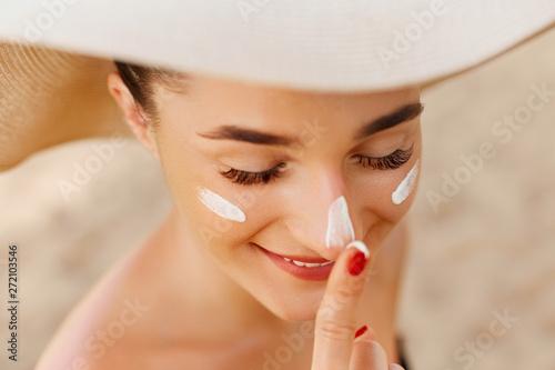 Suntan lotion woman applying sunscreen solar cream. Beautiful happy cute woman  applying suntan cream to her nose.