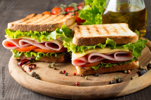 Keuken foto achterwand Snack Close-up photo of a club sandwich. Sandwich with meat, prosciutto, salami, salad, vegetables, lettuce, tomato, onion and mustard on a fresh sliced rye bread on wooden background. Olives background.