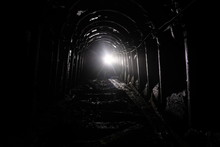 Dark Abandoned Coal Mine With Rusty Lining In Backlight