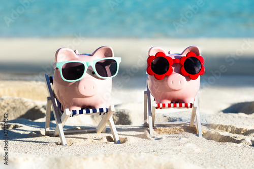 Fotomural  Two Pink Piggybanks With Sunglasses On Deck Chair At Beach