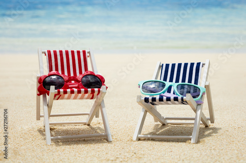 plakat Two Type Of Sunglasses On Deck Chair At Beach