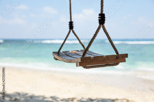 Poster Montagne An Empty Wooden Swing In Front Of Sea At Beach