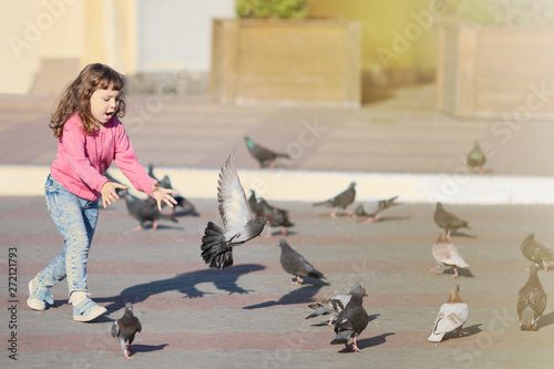 Deurstickers Stierenvechten Little girl running, flaunts the pigeons, childhood
