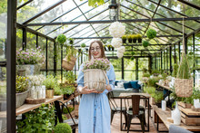 Portrait Of A Young Woman Standing With Lavender At The Entrance Of The Beautiful Greenhouse Or Flower Shop
