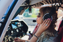 Female Pilot In Cockpit Of Helicopter Before Take Off. Young Woman Helicopter Pilot.