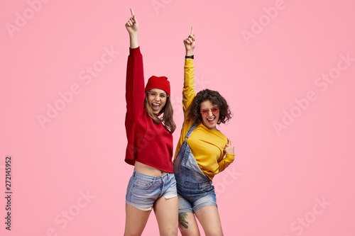 Fotografie, Tablou  Excited teen friends pointing up