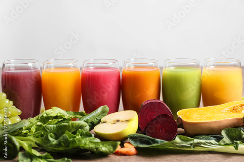 Foto auf Leinwand Saft Glasses with different juices and fresh ingredients on light background