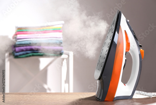 Fotografie, Obraz Modern iron with steam on table indoors. Space for text