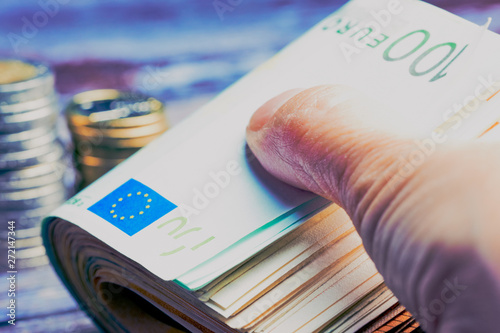 Obraz na plátně  female hand close up whilst holding bunch of Euro banknotes with one hundred not