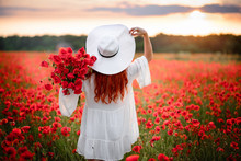 Red-haired Woman In White Hat Stands In Flowered Field Of Red Poppies With His Back To Camera