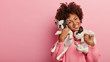 Happy female pet lover poses with two pedigree dogs, tilts head, has curly hair, wears pink sweater, isolated over rosy background, free space for your advertising. Friendship, people, animals concept