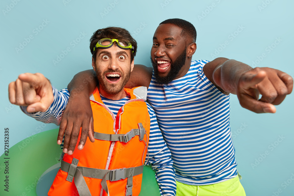 Fototapety, obrazy: Happy diverse guys embrace and point straightly at camera, have fun at beach, pose with life preserver, lifejacket, being in high spirit during sunny hot day, notice extreme parachute jumper