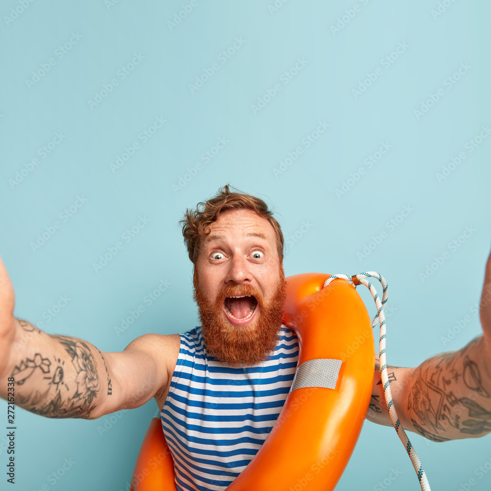 Fototapety, obrazy: Impressed happy surprised male swimmer shouts at camera, stares with bugged eyes, makes selfie, learns lifesaving skills and how to overcome potential hazards, poses with lifebuoy, stands indoor