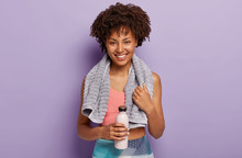 Shot Of Cheerful Female Runner Takes Break, Stands Indoor With Bottles Of Water, Has Satisfied Expression, Wipes Sweat With Towel, Isolated Over Purple Background. Sport And Fitness Concept.