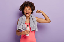Horizontal Shot Of Happy Afro Woman Shows Biceps, Satisfied After Active Training, Holds Bottle Of Water, Enjoys Healthy Lifestyle, Isolated Over Purple Background. Sport And Exercising Concept