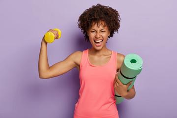 Smiješna sretna tamnoputa žena podiže ruku s bučicom, pokazuje bicepse, drži smotane fitnes prostirke, široko se smiješi, nosi ružičasti povremeni prsluk, izoliran na ljubičastoj pozadini. Kondicijski trening kod kuće