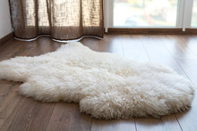 Sheep Skin On The Laminate Floor In The Room. Cozy Place Near The Window.