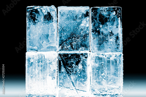 Textured frosty crystal clear ice blocks isolated on black background Wallpaper Mural
