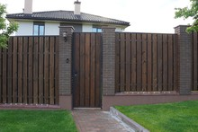 Brown Wooden Plank Fence And A Closed Door Outside
