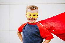 Little Boy Wearing Cape Dressed Up Like A Superhero