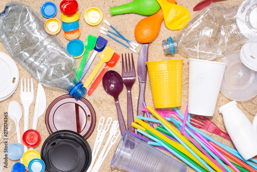 Fototapeta Disposable single use plastic objects such as bottles, cups, forks, spoons and drinking straws that cause pollution of the environment, especially oceans. Top view on sand