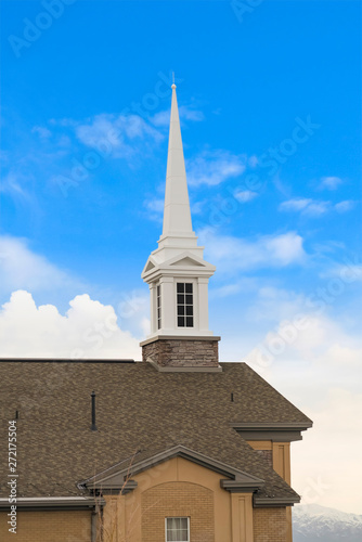 White steeple on top of the pitched roof of a church with brick exterior wall