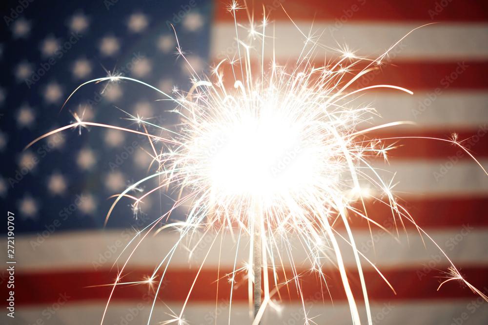 Fototapety, obrazy: Lit sparkler burning in front of American Flag