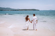 embracing romantic couplein white clothes looking on the sea on the Beautiful tropical beach vacation. Sea landscape with thai boat. Phuket. Thailand. Back view.