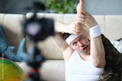 Valokuva  Blogger Man with Funny Face Doing Exercise for Leg