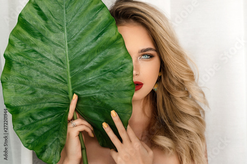 Obraz Spa and Beauty. Woman model with bright makeup and healthy skin with green leaf plant. Portrait of beautiful caucasian girl with big lips, closed eyes and sexy smile . - fototapety do salonu