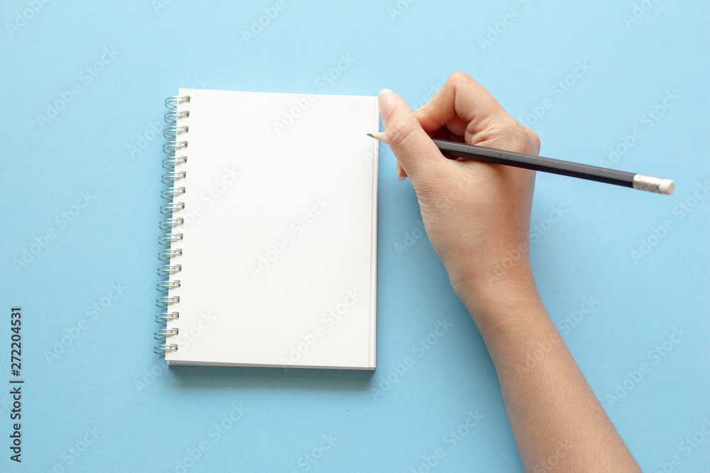 Fototapety, obrazy: woman hands writing in empty notebook at the blue desk. Flat lay top view.