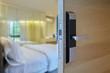 Digital door lock installed on wood door for security and access the room. Door wood texture with electronic door lock opened in front of blur bedroom. Selective focus.