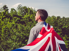 Attractive Man Waving A British Flag Against A Background Of Trees And Blue Sky. View From The Back, Close-up. National Holiday Concept