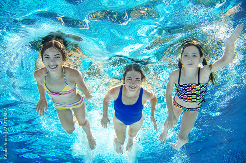 Family swims in pool underwater, happy active mother and children have fun under Canvas Print