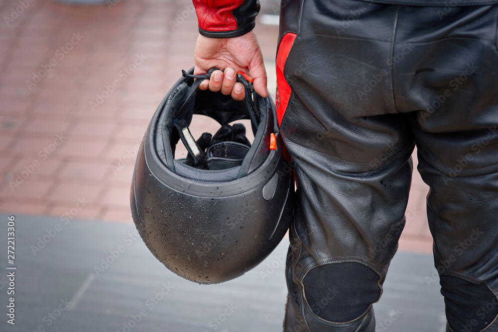 Fototapeta Biker in leather panths hold in hand black motorcycle helmet. Armor and special protective moto equipment for bikers and moto riders