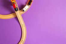 Toy Train And Wooden Rails On Purple Violet Background