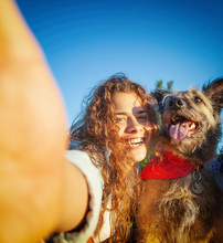 Beautiful Funny Curly Girl Takes A Selfie With Her Shaggy Dog In A Summer Park
