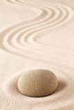 Meditation stone on sand background. Concept for zen, harmony and purity.