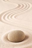 Fototapeta Kamienie - Meditation stone on sand background. Concept for zen, harmony and purity.