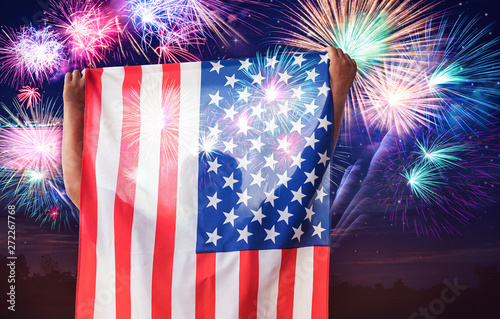 Photo  Man holding USA flag with fireworks