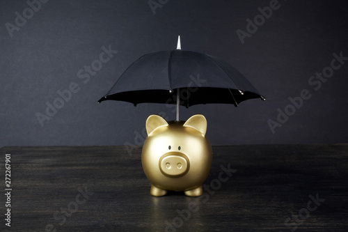 Fotografia  Gold Piggy bank with umbrella concept for finance insurance, protection, safe in
