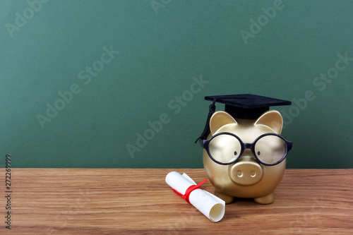 Leinwand Poster Gfold piggy bank with a grad cap and diploma in front of green chalkboard