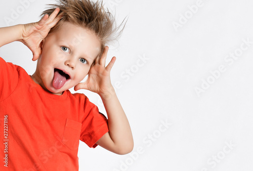 Foto op Aluminium Aap Kid boy in orange t-shirt jumped out and grimaces showing big ears with his hands and putting his tongue at us
