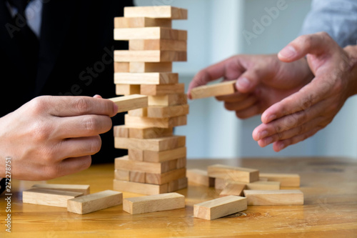 Businessmen Picking Wood Blocks To Fill The Missing Wood Blocks And